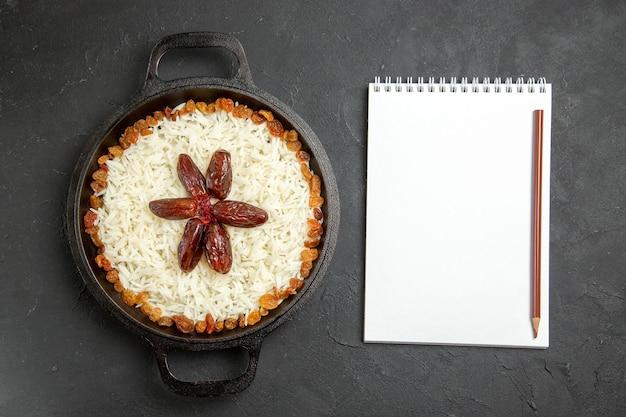 Bovenaanzicht gekookte rijst met rozijnen in pan op donkere oppervlakte eten rijst oosterse maaltijd diner