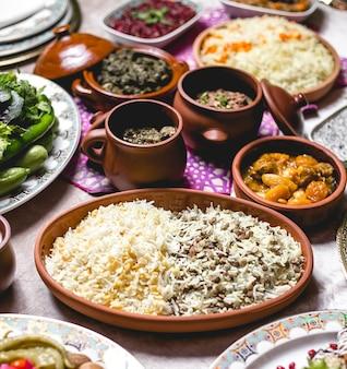 Bovenaanzicht gekookte rijst op een bord met loby en bonen en een verscheidenheid aan vleessaus