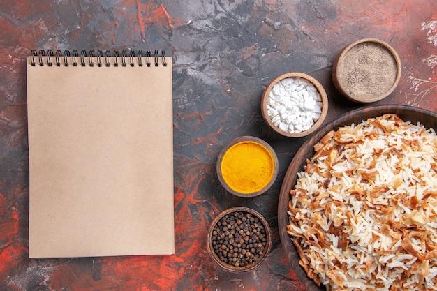 Bovenaanzicht gekookte rijst samen met kruiderijen op de fotomaaltijd van de donkere ondergrond