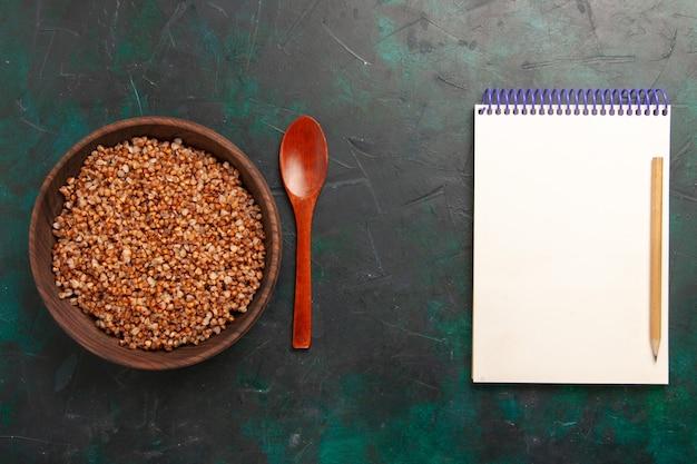 Bovenaanzicht gekookte smakelijke boekweitmaaltijd in bruine houten plaat op het donkergroene oppervlak
