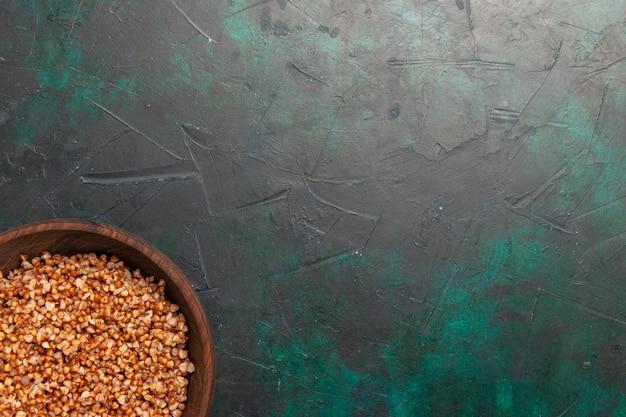 Bovenaanzicht gekookte smakelijke boekweitmaaltijd in bruine plaat op het donkergroene oppervlak