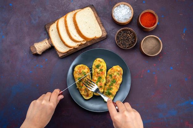 Bovenaanzicht gekookte smakelijke pompoenen met kruiden en broodbroodjes op het donkerpaarse bureau.