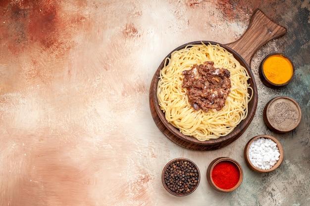 Bovenaanzicht gekookte spaghetti met gehakt op lichte tafelschotel pastadeeg