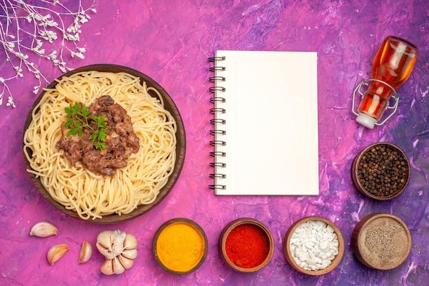 Bovenaanzicht gekookte spaghetti met gehakt op roze tafel pasta kruiden deegschotel