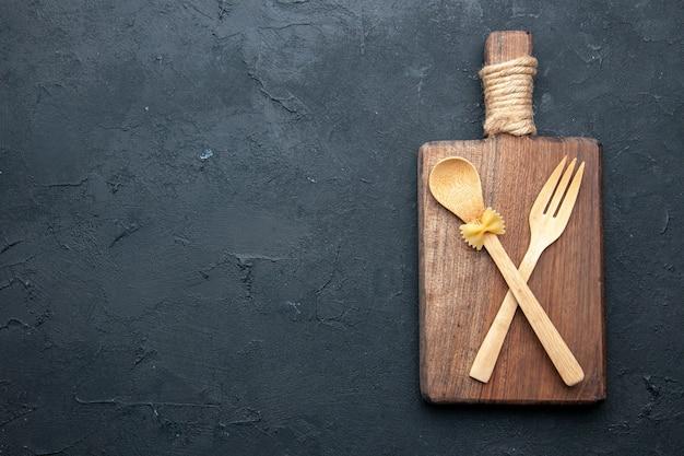 Bovenaanzicht gekruiste houten lepel en vork op houten bord op zwarte tafel kopie plaats