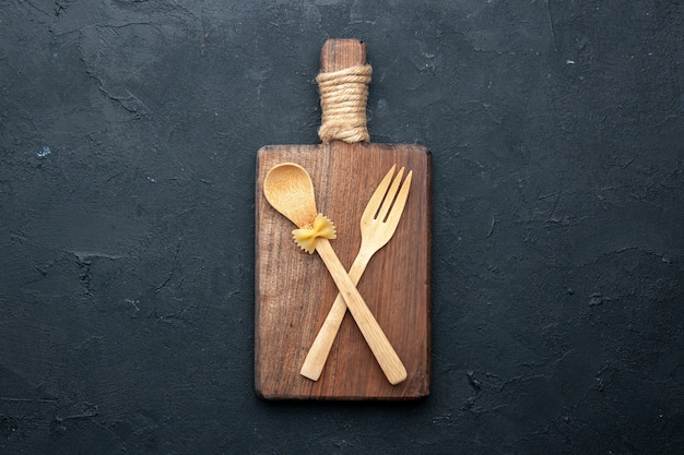 Bovenaanzicht gekruiste houten lepel en vork op houten serveerplank op donkere tafel kopie plaats
