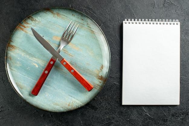 Bovenaanzicht gekruiste vork en mes op notebook met ronde plaat