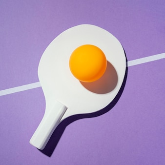 Bovenaanzicht gele bal op pingpongpeddel
