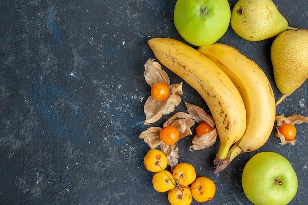 Bovenaanzicht gele bananen paar bessen met groene appels peren op de donkerblauwe achtergrond fruit bes verse gezondheid vitamine
