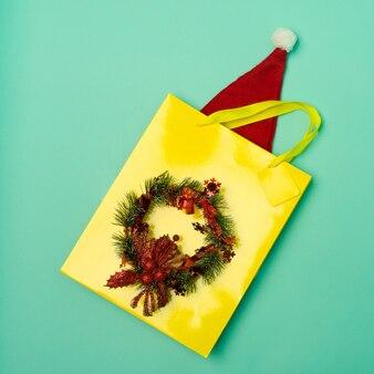 Bovenaanzicht gele boodschappentas met kerstmuts op tafel met de feestdagen
