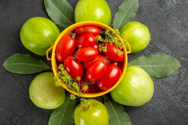 Bovenaanzicht gele emmer gevuld met kerstomaatjes en dille bloemen omgeven met groene tomaten op donkere achtergrond