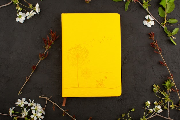 Bovenaanzicht gele foto samen met bloemen op de donkere vloer