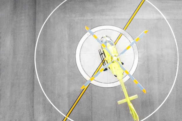 Bovenaanzicht gele helikopter op helikopterplatform