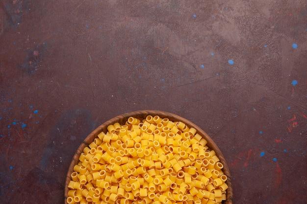 Bovenaanzicht gele italiaanse pasta rauw weinig gevormd op de donkere paarse achtergrond pasta eten rauwe deeg maaltijd