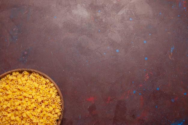 Bovenaanzicht gele italiaanse pasta rauw weinig gevormd op het donkerpaarse achtergrond pasta eten rauwe maaltijd deeg