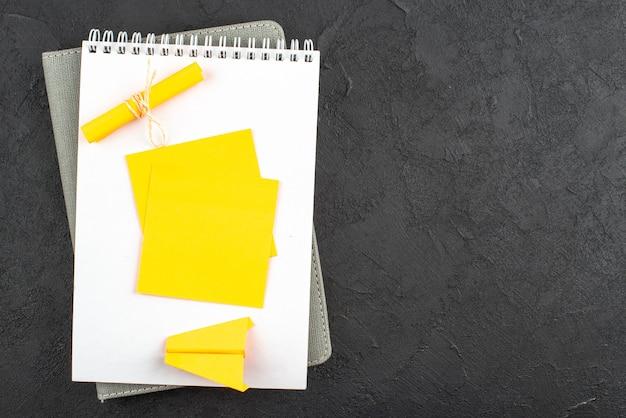 Bovenaanzicht gele kleverige nota op wit notitieblok op donkere achtergrond