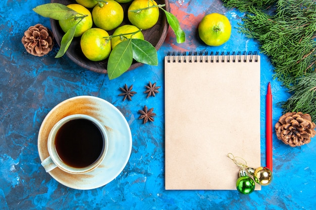 Bovenaanzicht gele mandarijnen met bladeren in houten kom kladblok rood potlood xmas ornamenten een kopje thee anijs op blauwe ondergrond