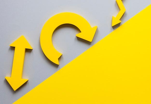 Bovenaanzicht gele pijlen en karton op witte achtergrond