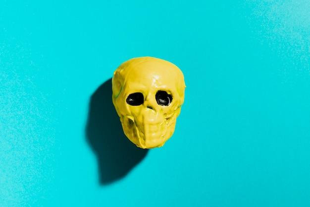 Bovenaanzicht gele schedel op blauwe achtergrond