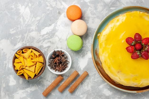 Bovenaanzicht gele stroopcake met franse macarons op witte achtergrond