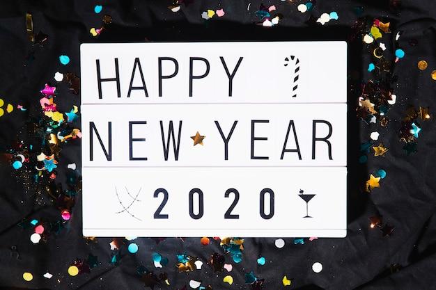 Bovenaanzicht gelukkig nieuwjaar teken en confetti