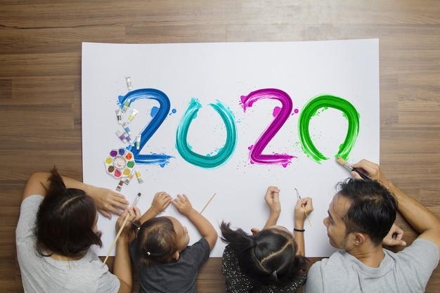 Bovenaanzicht gelukkige familie liggend op vloer met schilderij 2020 gelukkig nieuwjaar op papier