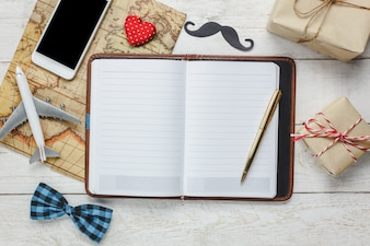 Bovenaanzicht Gelukkige Vaderdag met travel.White mobiele telefoon en notitieboekje op rustieke houten achtergrond. Accessoires met kaart, vliegtuig, snor, vintage strikje, pen, heden, rood hart.