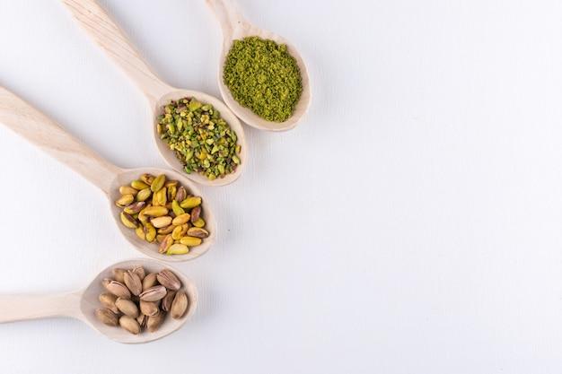 Bovenaanzicht gemalen, gemalen, gemalen of gekorrelde pistaches in houten lepels op wit