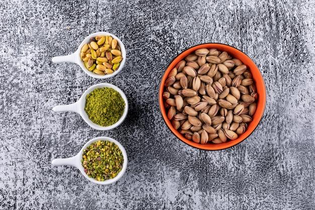 Bovenaanzicht gemalen, gemalen, gemalen pistachenoten in een kom op grijze textuur