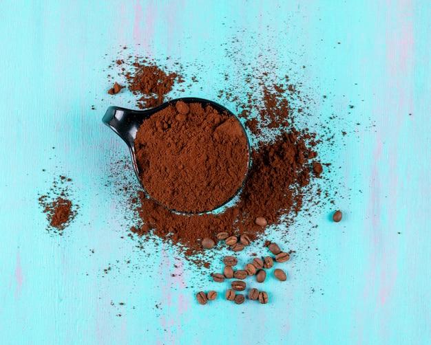 Bovenaanzicht gemalen koffie in cup met koffiebonen op blauwe oppervlak