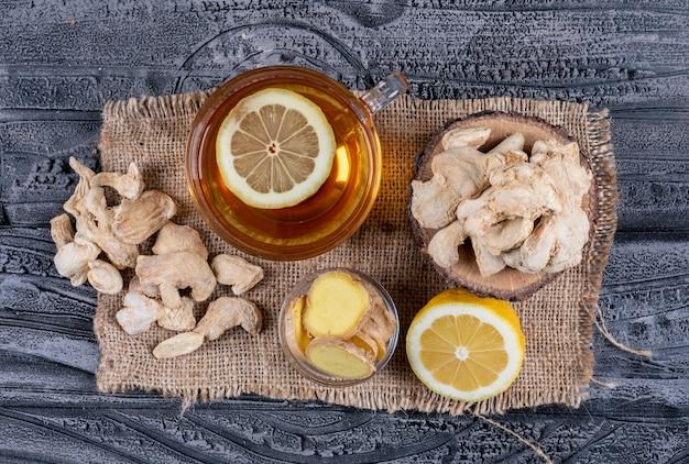 Bovenaanzicht gember met thee, citroen en gember segmenten op zak doek en donkere houten achtergrond. horizontaal
