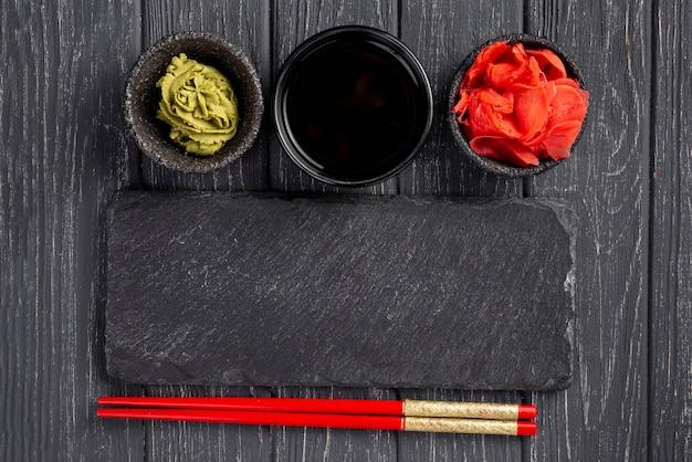 Bovenaanzicht gember wasabi en sojasaus kommen en eetstokjes