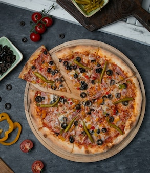 Bovenaanzicht gemengd ingrediënt pizza in plakjes gesneden.