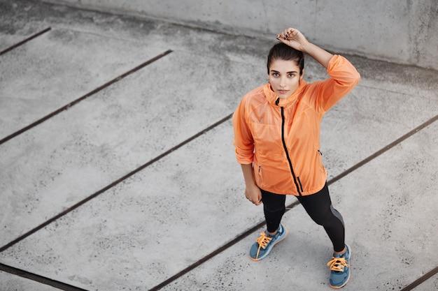 Bovenaanzicht gemotiveerde zelfverzekerde jonge brunette vrouw in oranje ru