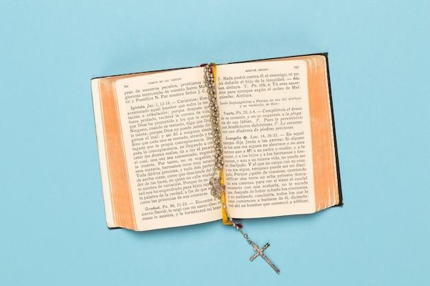 Bovenaanzicht geopend heilig boek met ketting