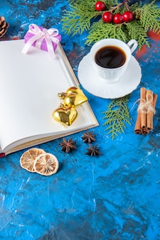 Bovenaanzicht geopend notebook dennenboom takken kegels kerstboom speelgoed op blauwe ondergrond