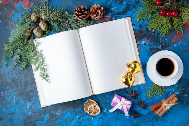 Bovenaanzicht geopend notitieboekje dennenboom takken kegels kerstboom speelgoed op blauwe achtergrond gratis plaats