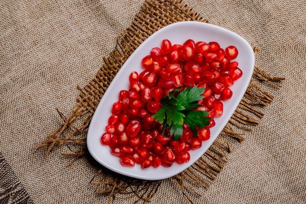 Bovenaanzicht gepelde granaatappel met peterselie