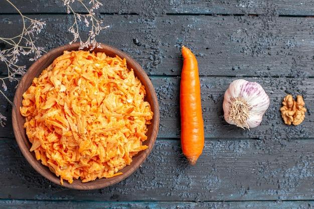 Bovenaanzicht geraspte wortelsalade in bruine plaat op donkerblauw rustiek bureau gezondheidssalade rijpe groenten dieetkleur