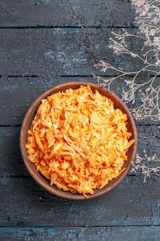 Bovenaanzicht geraspte wortelsalade in bruine plaat op het donkerblauwe rustieke bureau gezondheid salade kleur rijp dieet groente