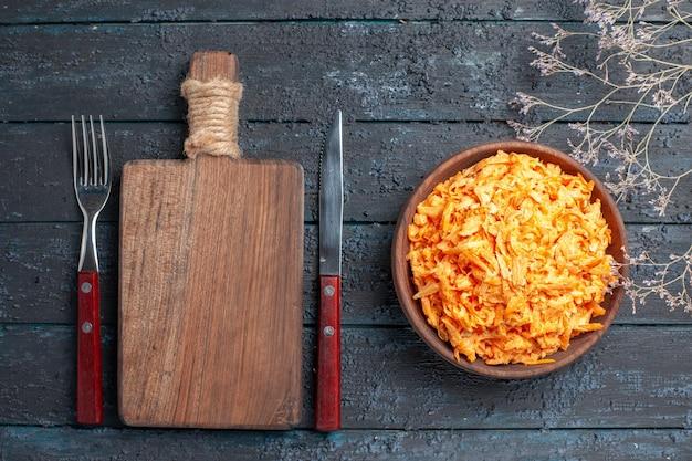 Bovenaanzicht geraspte wortelsalade in bruine plaat op het donkerblauwe rustieke bureau gezondheidssalade rijp plantaardig dieetkleur