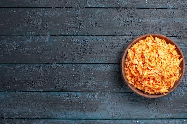Bovenaanzicht geraspte wortelsalade in plaat op donkerblauwe rustieke bureausalade kleur gezondheidsdieet groente