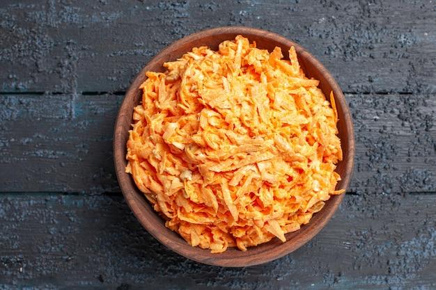 Bovenaanzicht geraspte wortelsalade in plaat op donkerblauwe rustieke bureausalade kleur rijp gezondheidsdieet groente