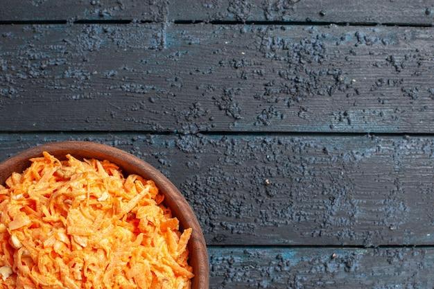 Bovenaanzicht geraspte wortelsalade in plaat op donkerblauwe rustieke bureausalade kleur rijpe gezondheidsdieet groenten