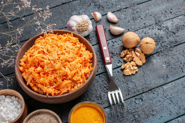 Bovenaanzicht geraspte wortelsalade met knoflook en smaakmakers op donkerblauwe rustieke vloer gezondheid kleur salade rijp plantaardig dieet