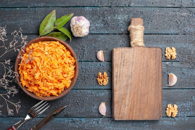 Bovenaanzicht geraspte wortelsalade met knoflook en walnoten op het donkere rustieke bureau gezondheid groentedieet salade kleur rijp
