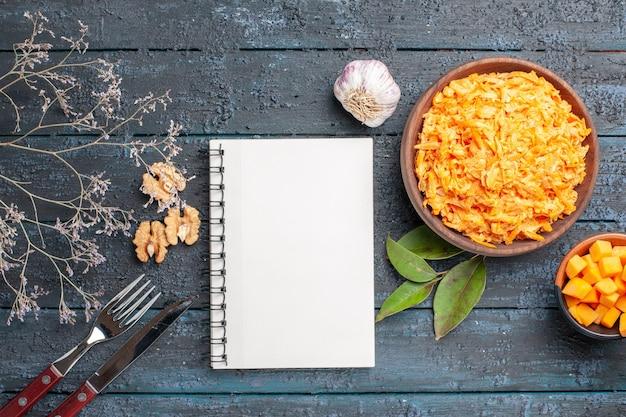 Bovenaanzicht geraspte wortelsalade met knoflook en walnoten op het donkere rustieke bureau gezondheidsdieet salade rijp oranje kleur
