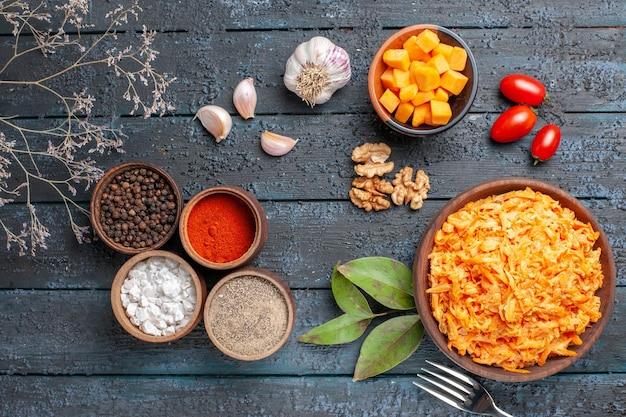 Bovenaanzicht geraspte wortelsalade met knoflook, walnoten en kruiden op het donkere bureau gezondheidsdieet oranje kleur rijpe salade