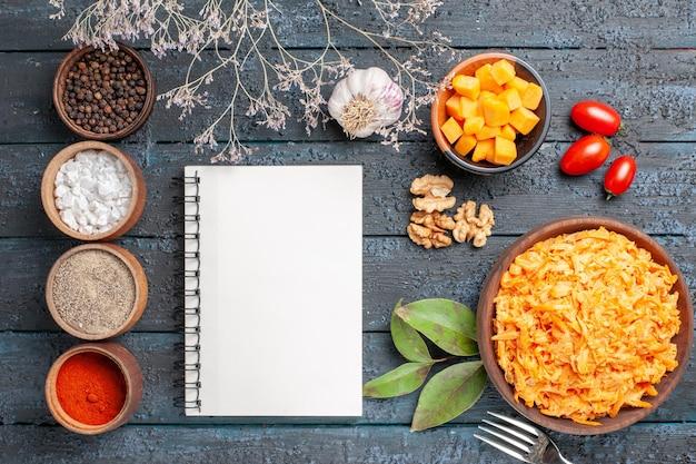 Bovenaanzicht geraspte wortelsalade met knoflook, walnoten en kruiden op het donkere bureau gezondheidsdieet salade oranje kleur rijp