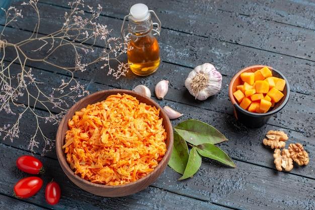 Bovenaanzicht geraspte wortelsalade met knoflookwalnoten op donkere achtergrond gezondheidsdieet oranje kleur rijpe salade